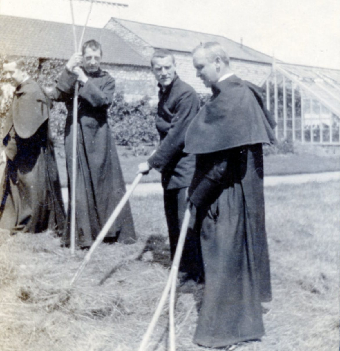 Old image of monks raking hay