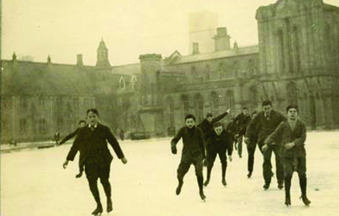 Old image of boys ice skating outside of abbey