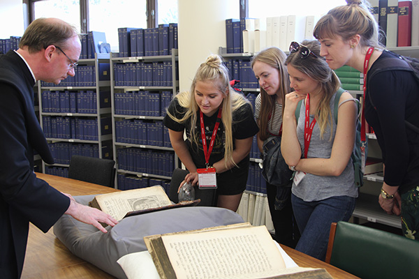 Students looking at old books in library