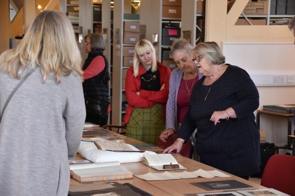 Women talking and looking at old books
