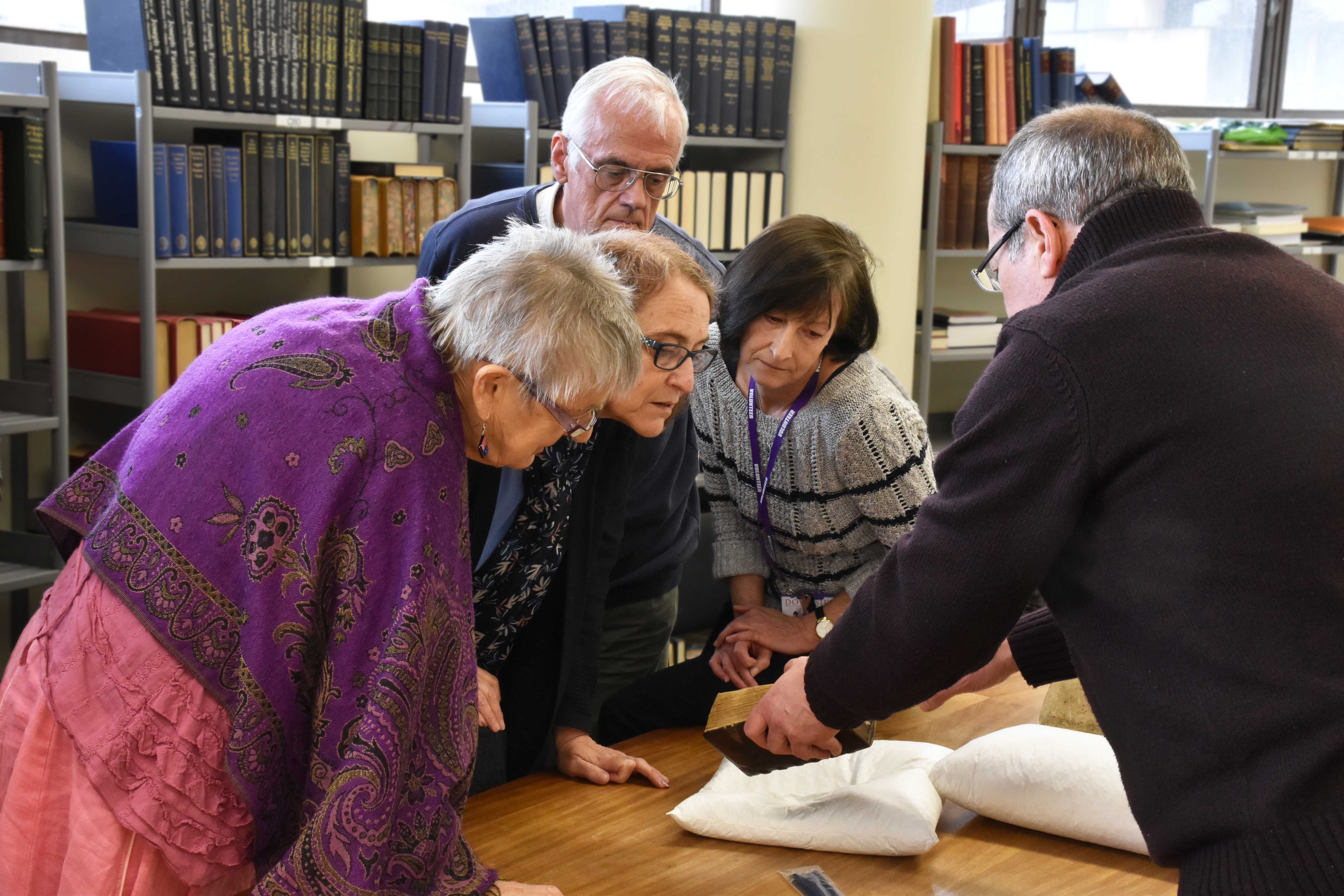 Volunteers looking at book