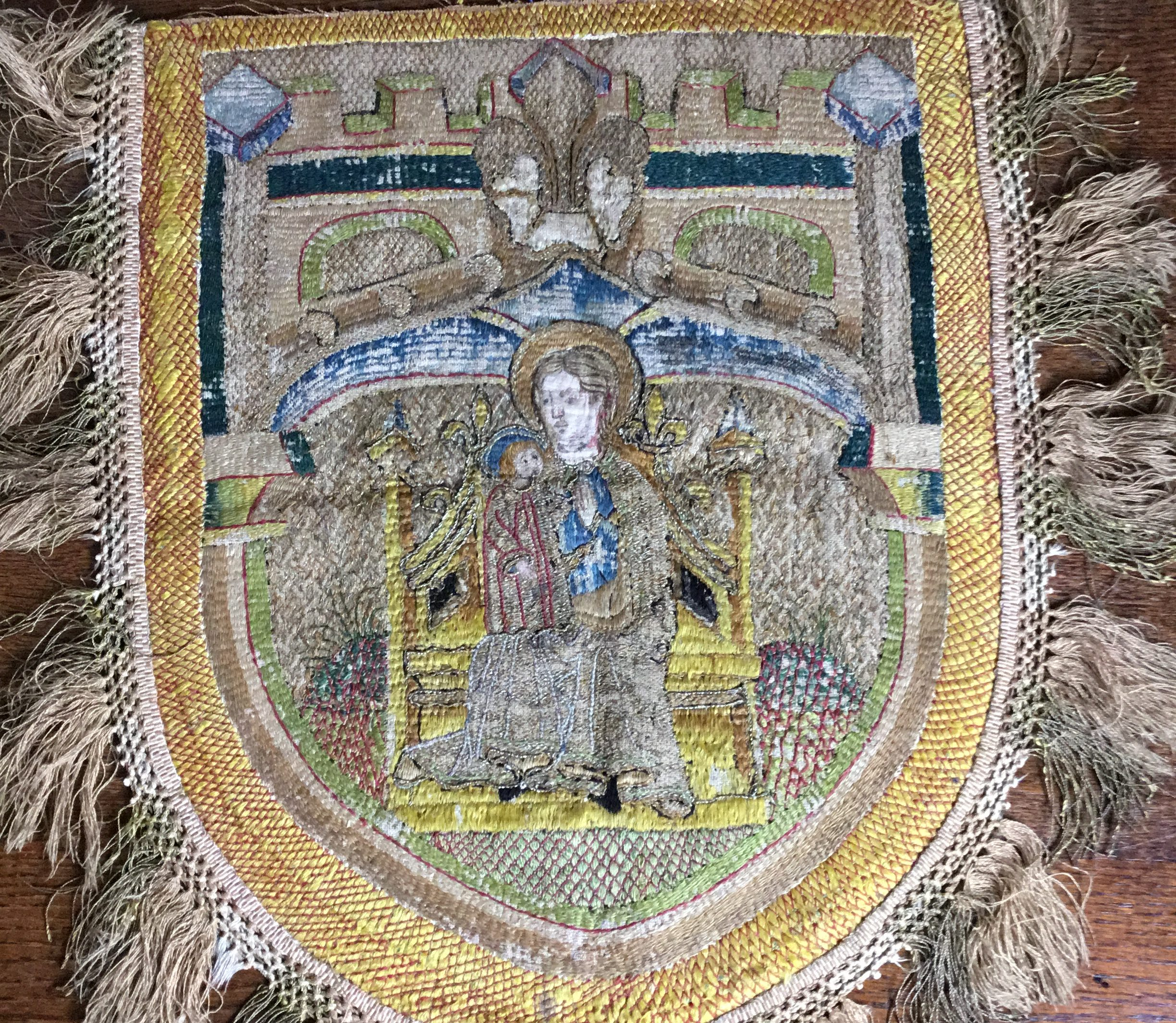 Embroidered image of Mary and Jesus in crest