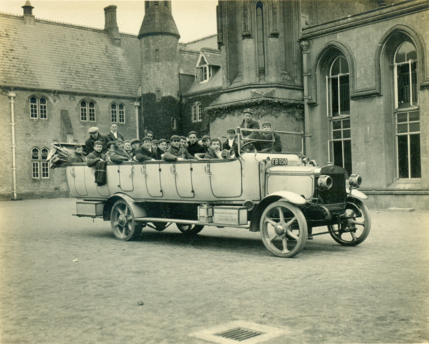 Old photo of large topless car/ bus with pupils inside.